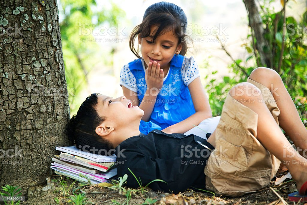 Boy lying under tree with his sister and smiling stock photo
