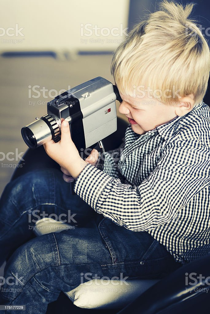 Boy makes a video with an old retro camera royalty-free stock photo