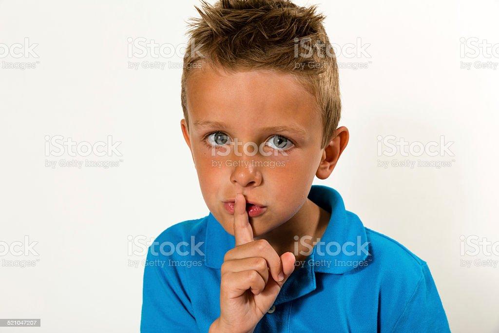 Boy making keep quiet gesture stock photo
