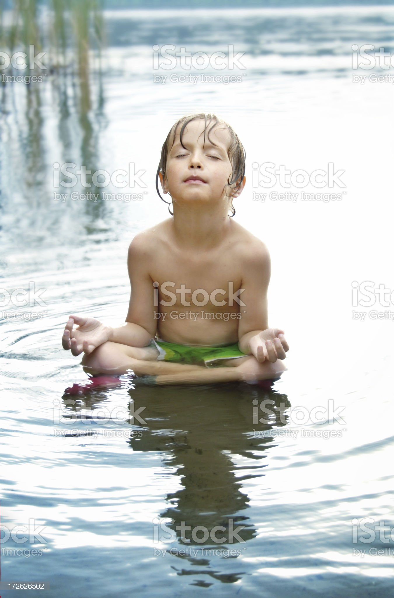 Boy meditating in water (with Background) royalty-free stock photo