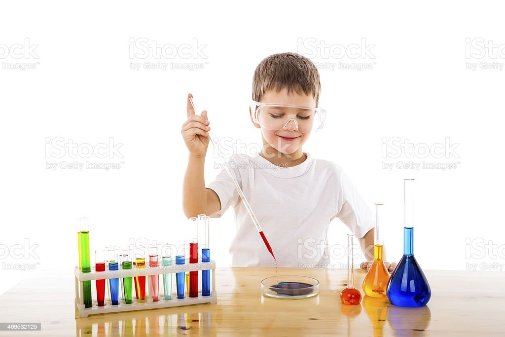 Boy mixes chemicals in the lab stock photo