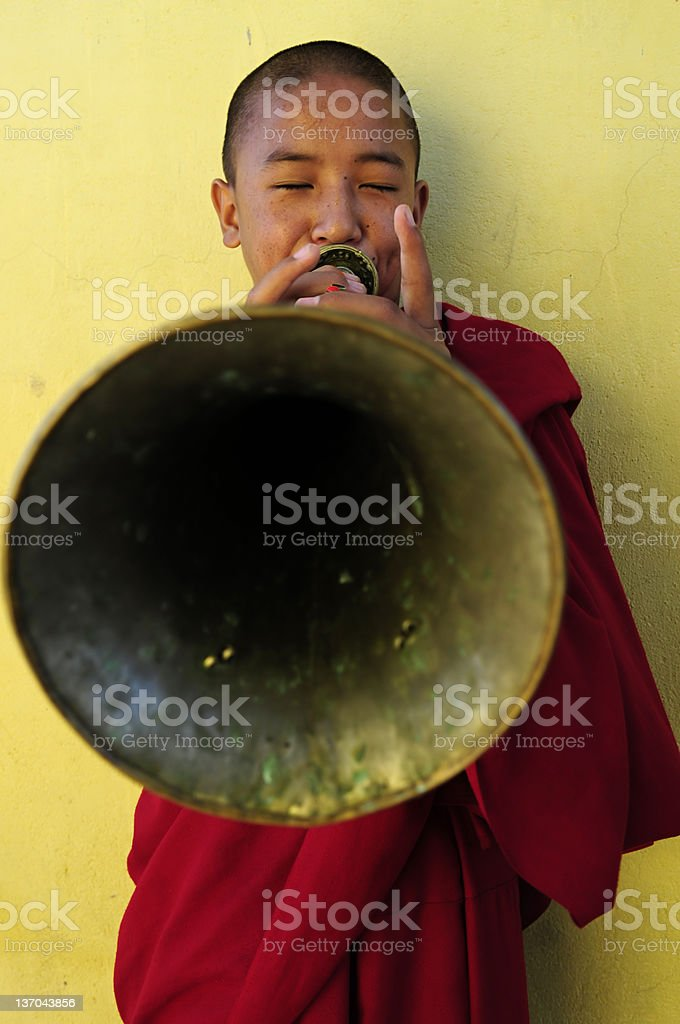 Boy monk playing Tibetan Buddhist trumpet royalty-free stock photo