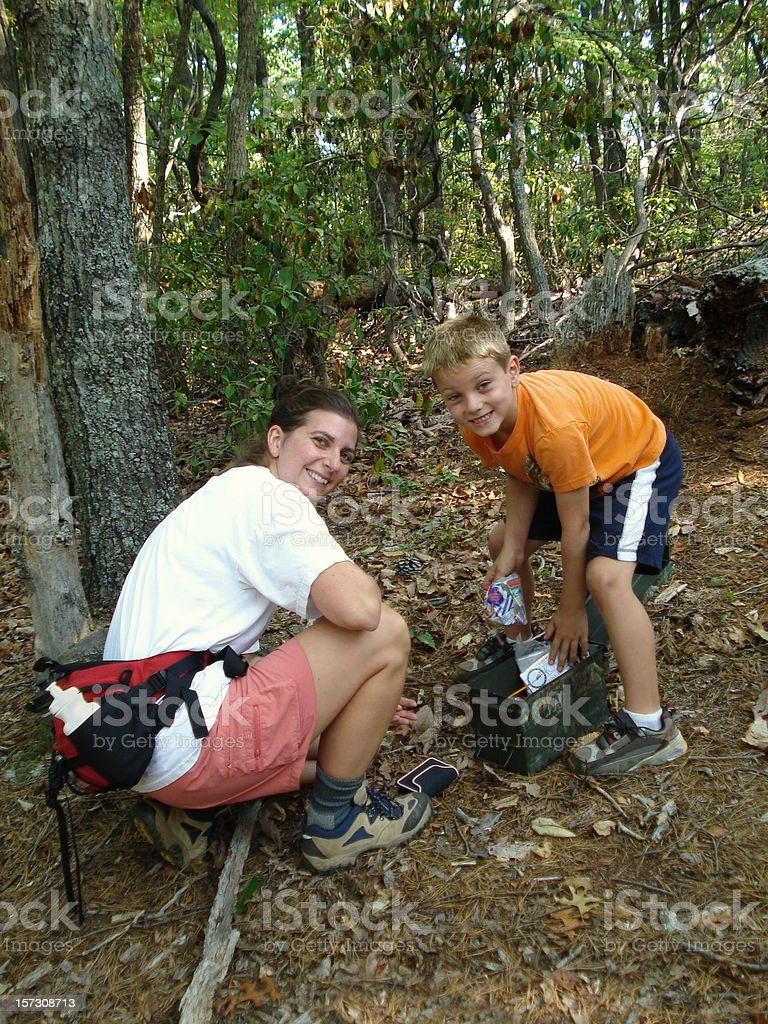 Boy & Mother (Family) Geocaching in the woods. stock photo