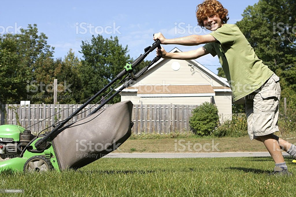 Boy Mowing Lawn stock photo