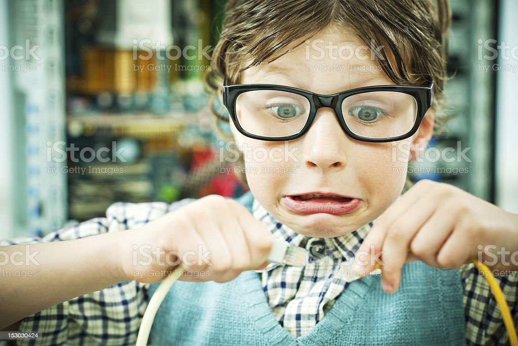 Boy nerd is looking with frustration at two wires. stock photo