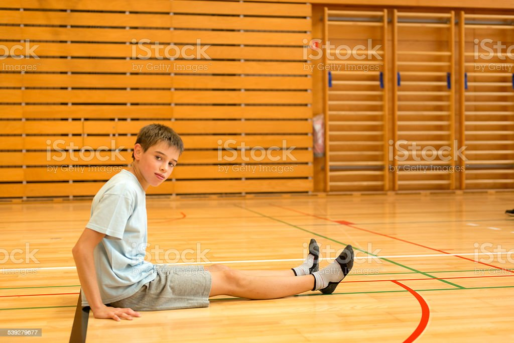 Eleven years old boy sitting on the floor in the school gymnasium,...