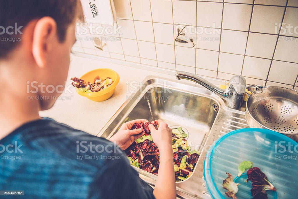 Boy of Twelve Cleaning Radicchio in Home Kitchen, Europe stock photo