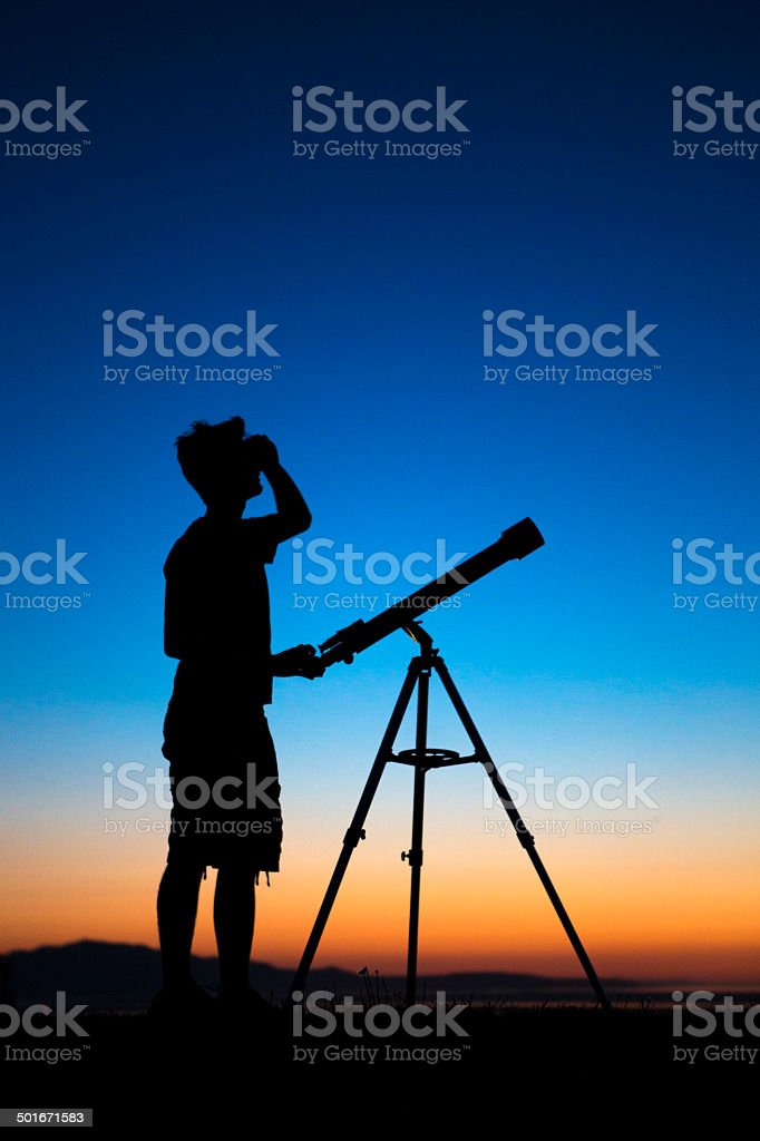 Boy on a clear night looking thru a telescope stock photo