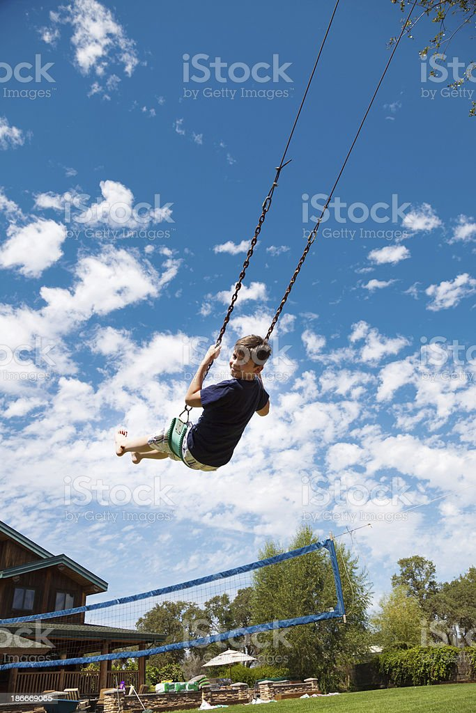 Boy on a long swing stock photo