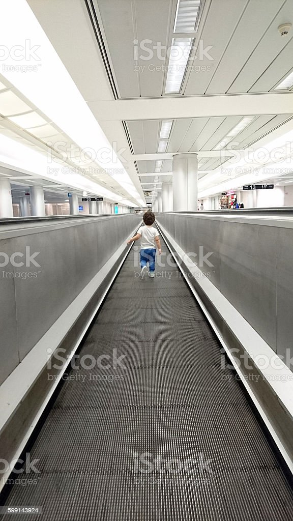 Boy on a moving walkway in Airport. stock photo