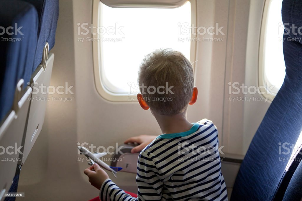 Boy on a plane looking out the window royalty-free stock photo