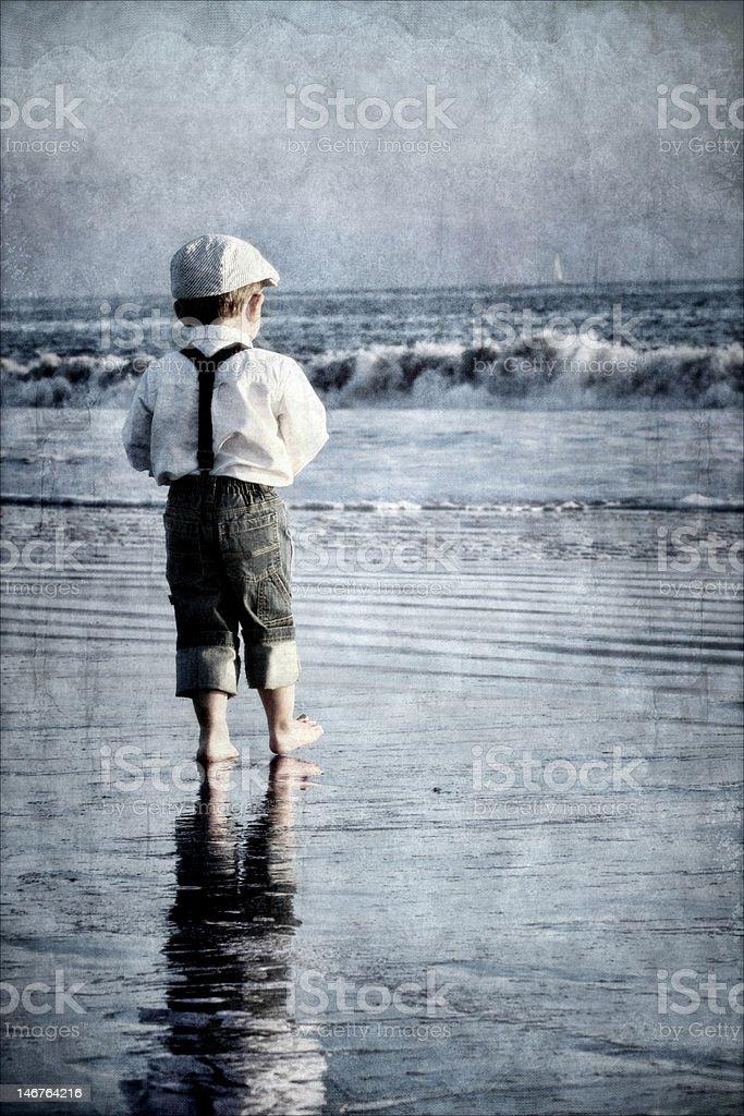 Boy on beach looking at sailboat stock photo