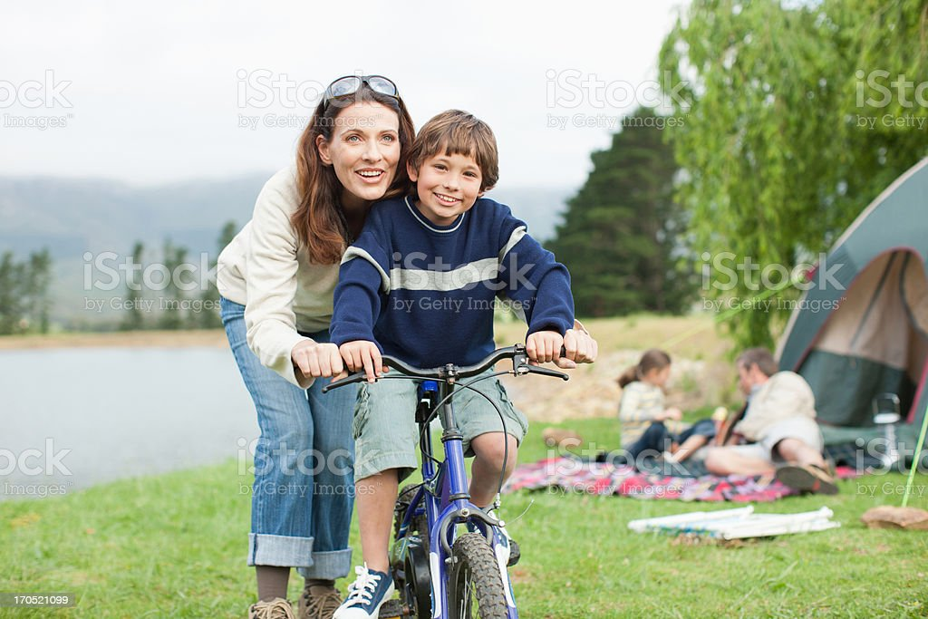 Boy on bicycle while on family camping trip stock photo