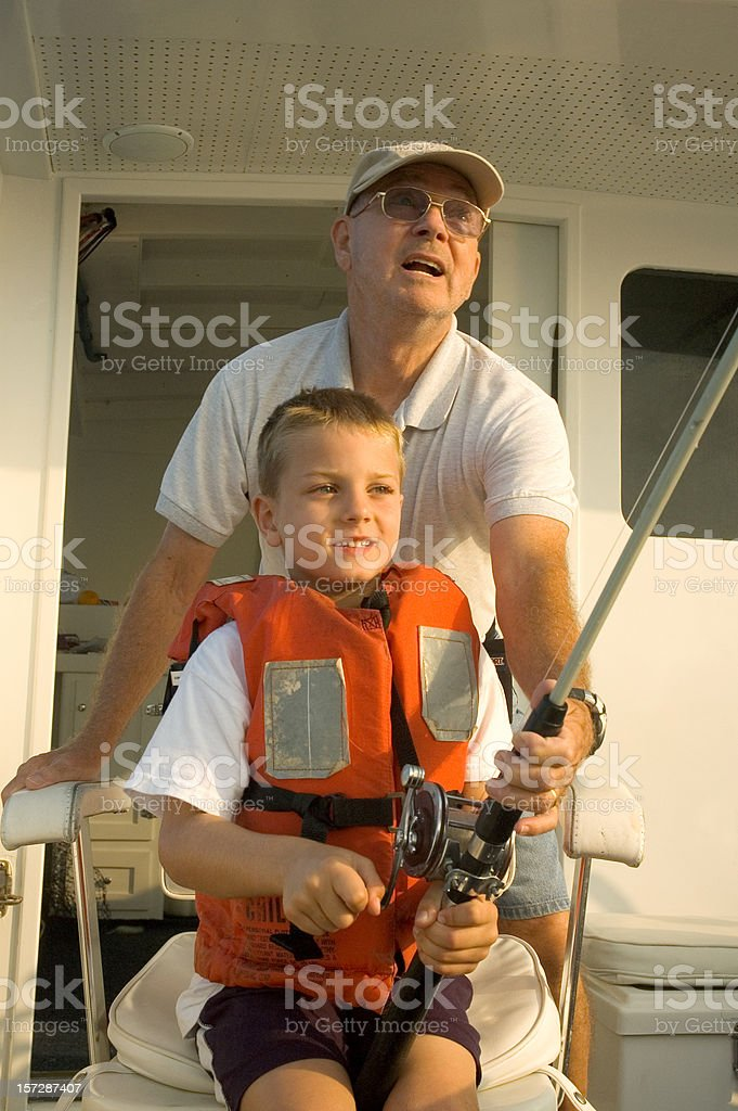 Boy On Charter Boat Fishing With Grandpa  (Active Senior Citizen) royalty-free stock photo
