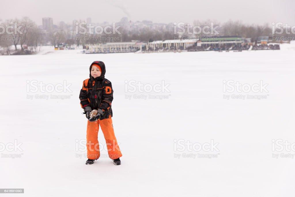 Boy on frozen lake stock photo