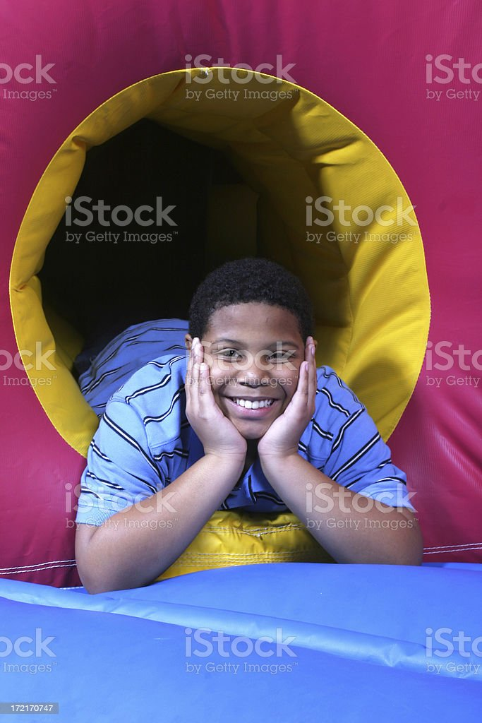 Boy on inflatable slide grins royalty-free stock photo
