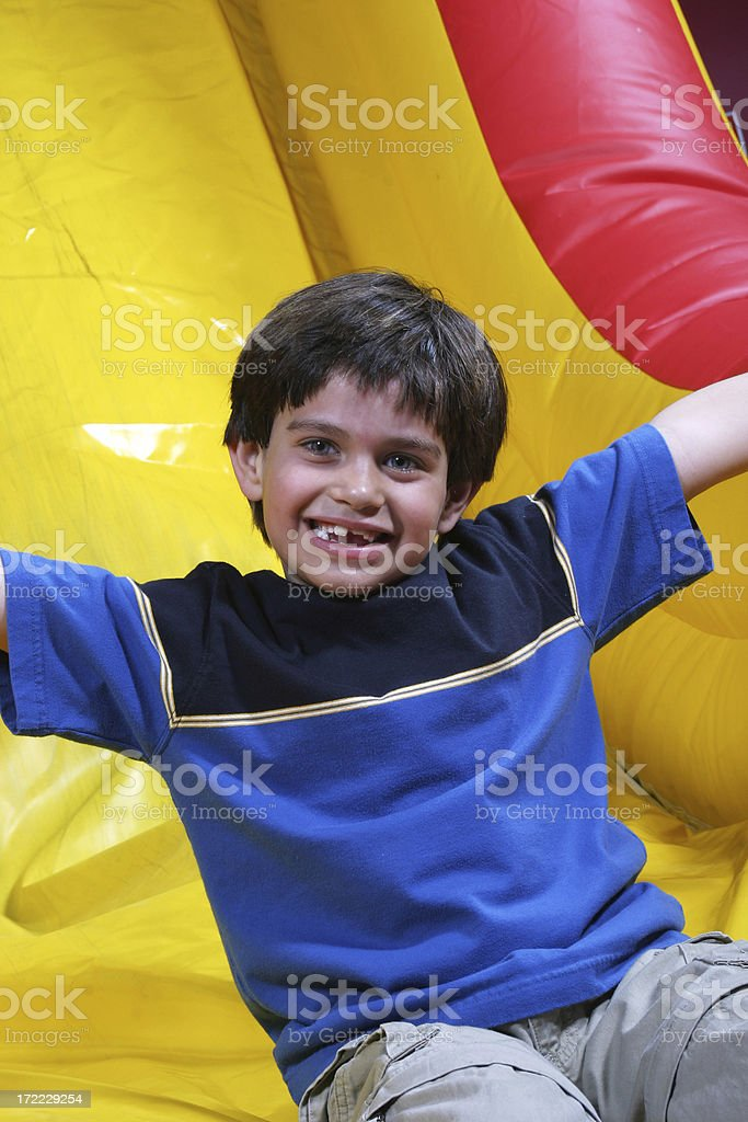 Boy on inflatable slide smiles royalty-free stock photo