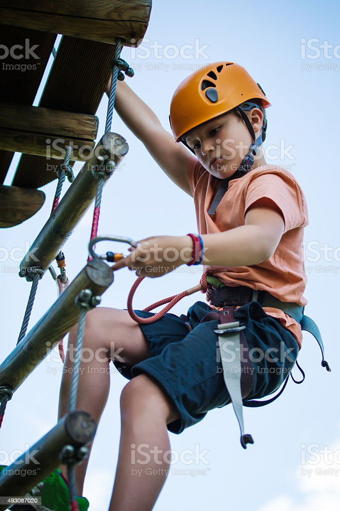 Boy on ladder in adventure park stock photo