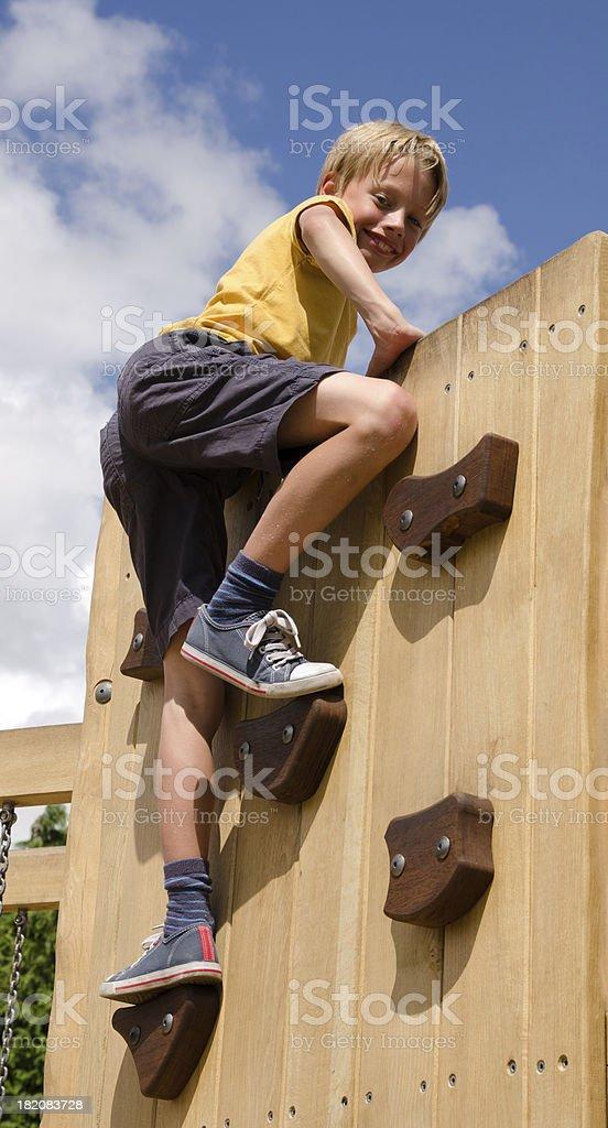 Boy on playground climbing wall stock photo