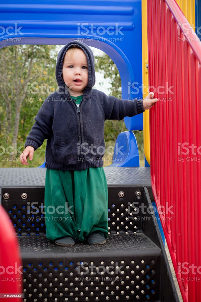 Boy on playground slide stock photo