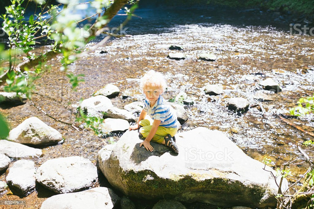 Boy on Rock in River stock photo
