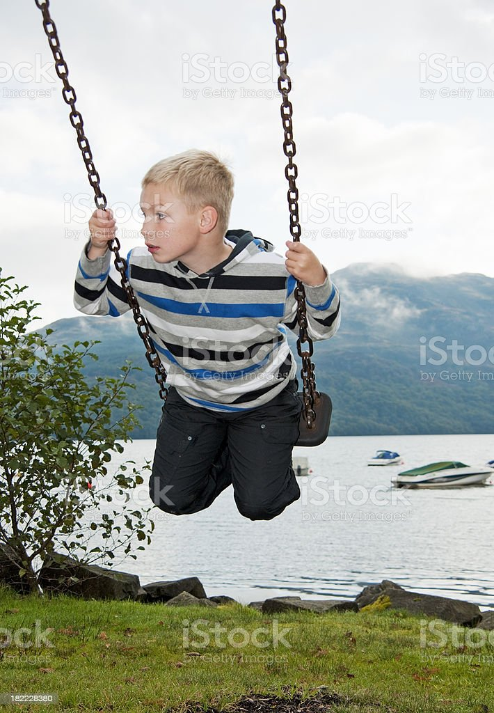 boy on swing at loch lomond shore royalty-free stock photo