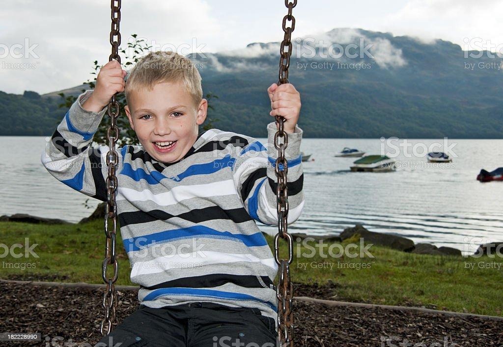 boy on swing at loch lomond shore royalty-free stock photo