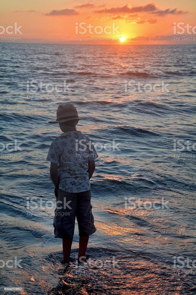 Boy  on the beach at the sundown stock photo