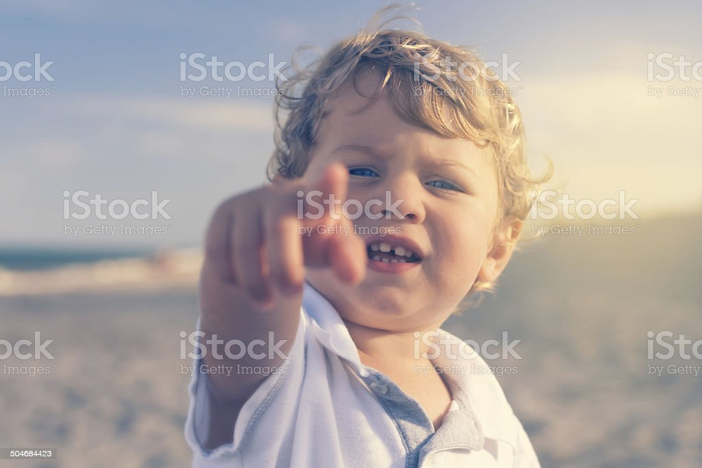 Boy on the beach pointing finger to a camera royalty-free stock photo