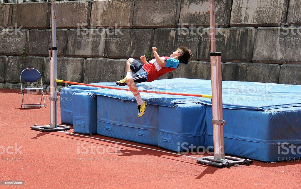 Boy on the high jump. stock photo