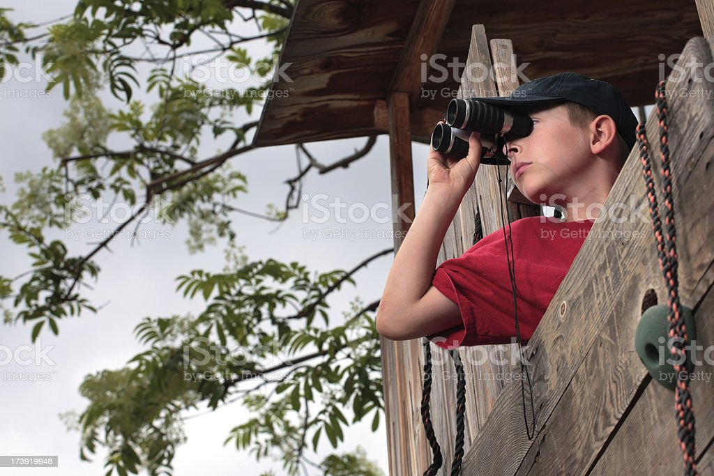 Boy on the lookout from treehouse stock photo