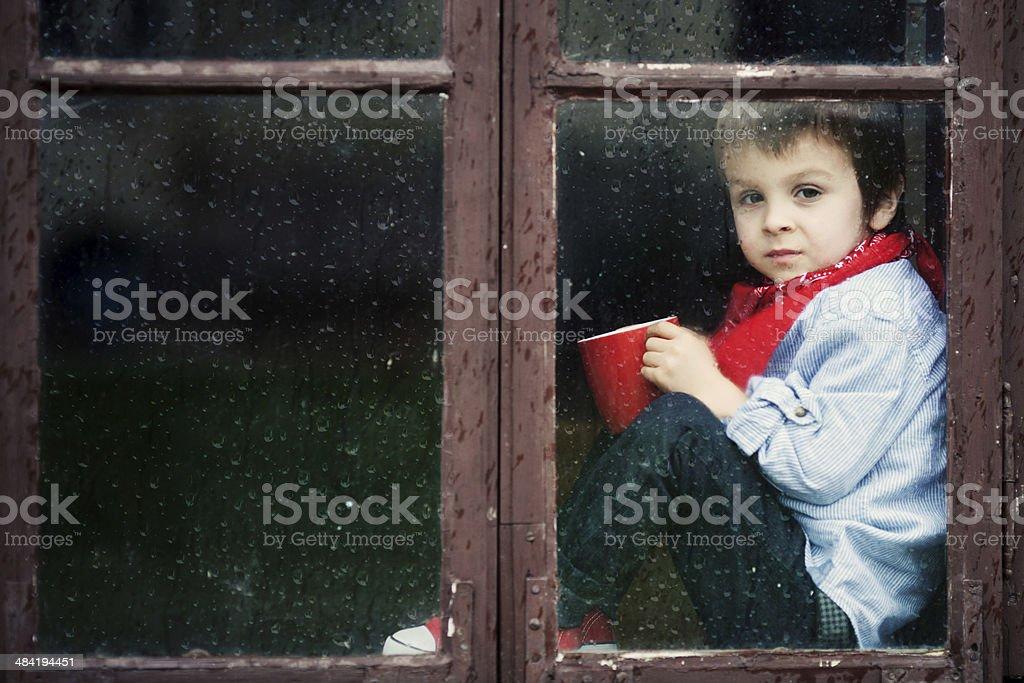 Boy on the window, smiling and drinking tea, having fun stock photo