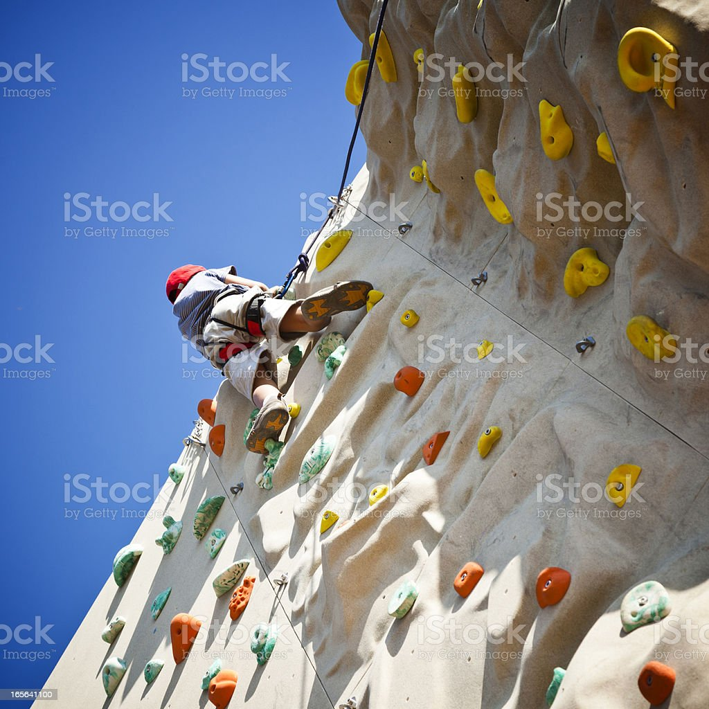 Boy on top of climbing wall stock photo