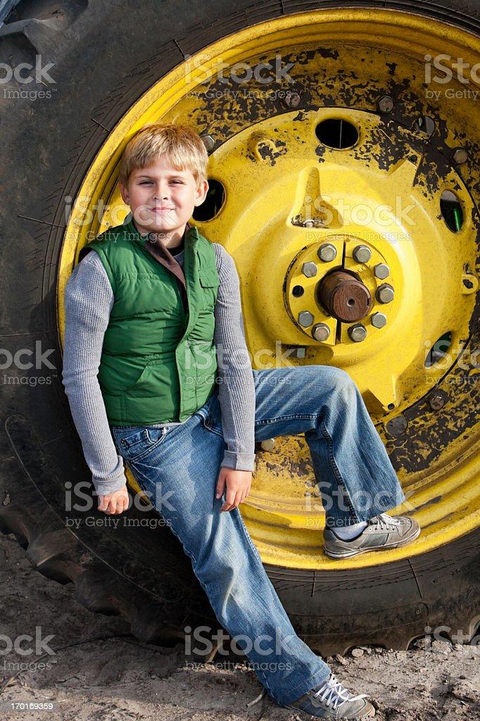Boy on tractor wheel stock photo