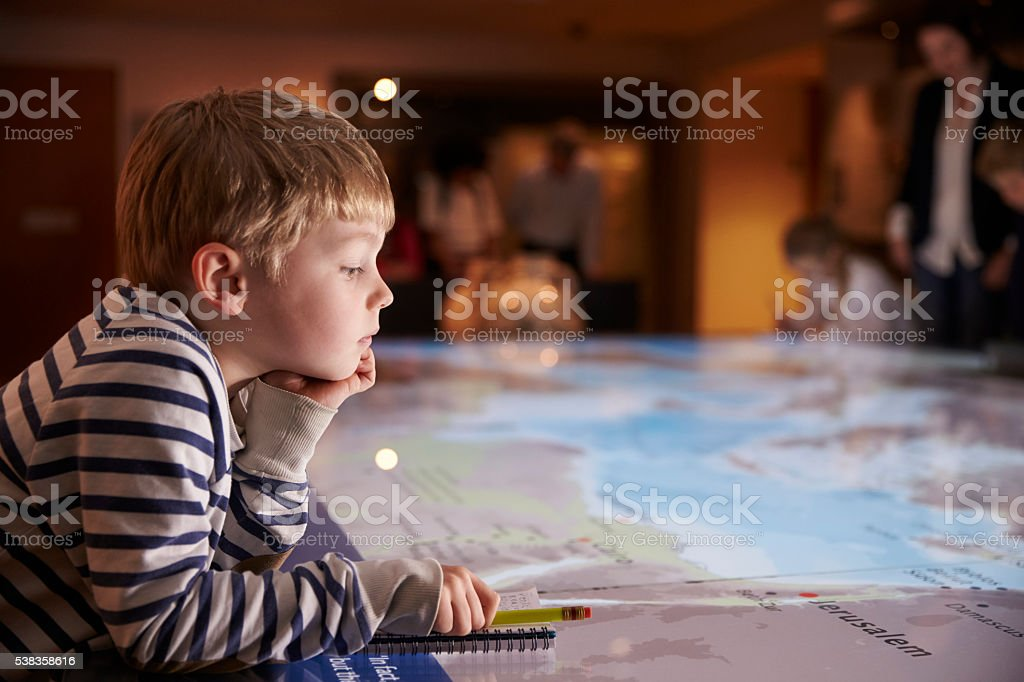 Boy On Trip To Museum Looking At Map And Writing In stock photo