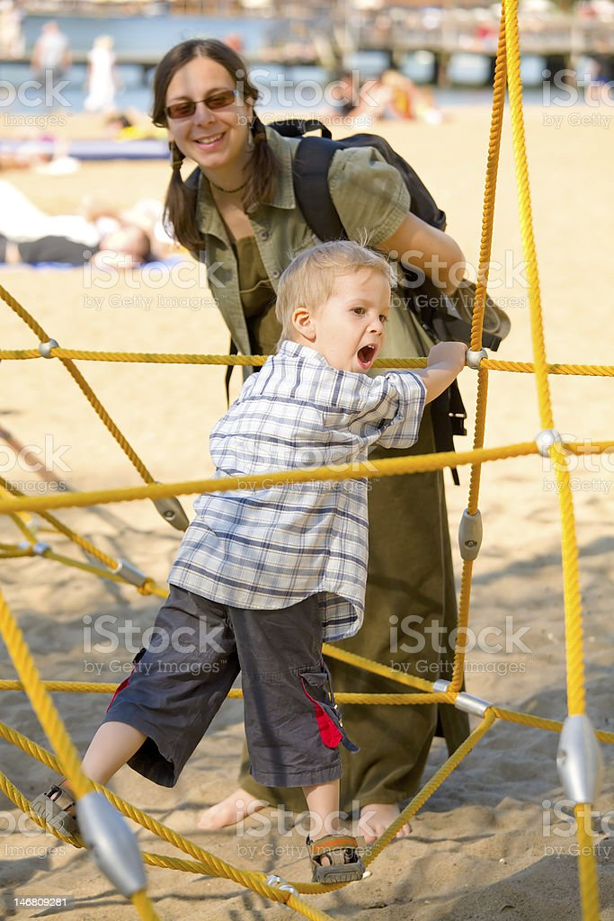 Boy on yellow ropes with mom royalty-free stock photo