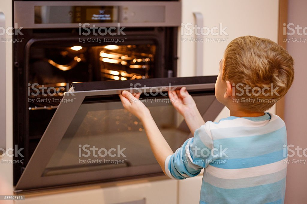 Boy opening oven, baking cookies stock photo
