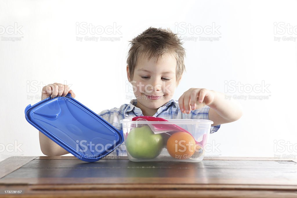 A boy opens a Tupperware box with an apple and orange inside stock photo