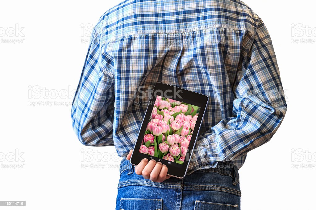 Boy or man hiding tulips screen tablet computer behind back royalty-free stock photo