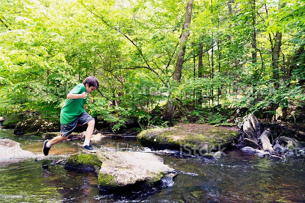 Boy Outdoors Jumping Across River Rocks in Woods stock photo
