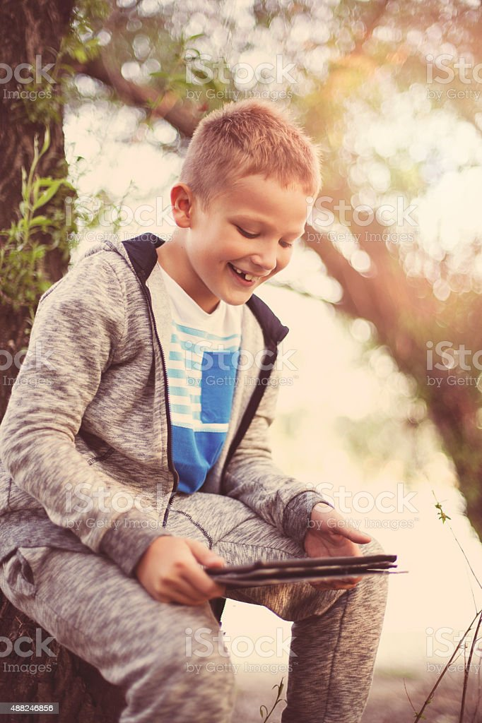 Boy outdoors with a digital tablet digital tablet stock photo
