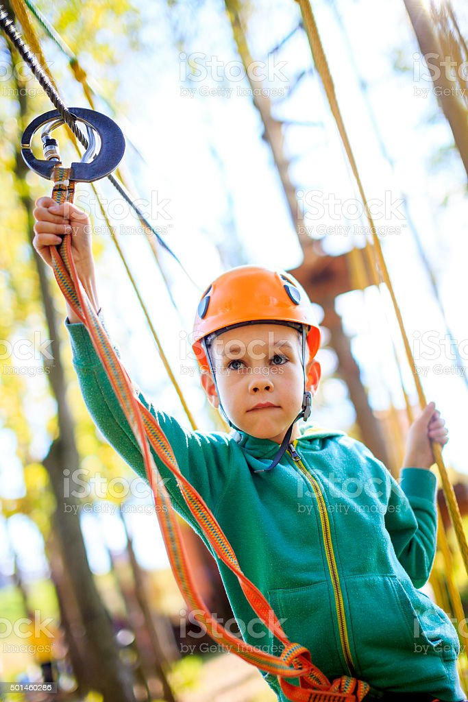 boy overcomes the obstacle course in rope park stock photo