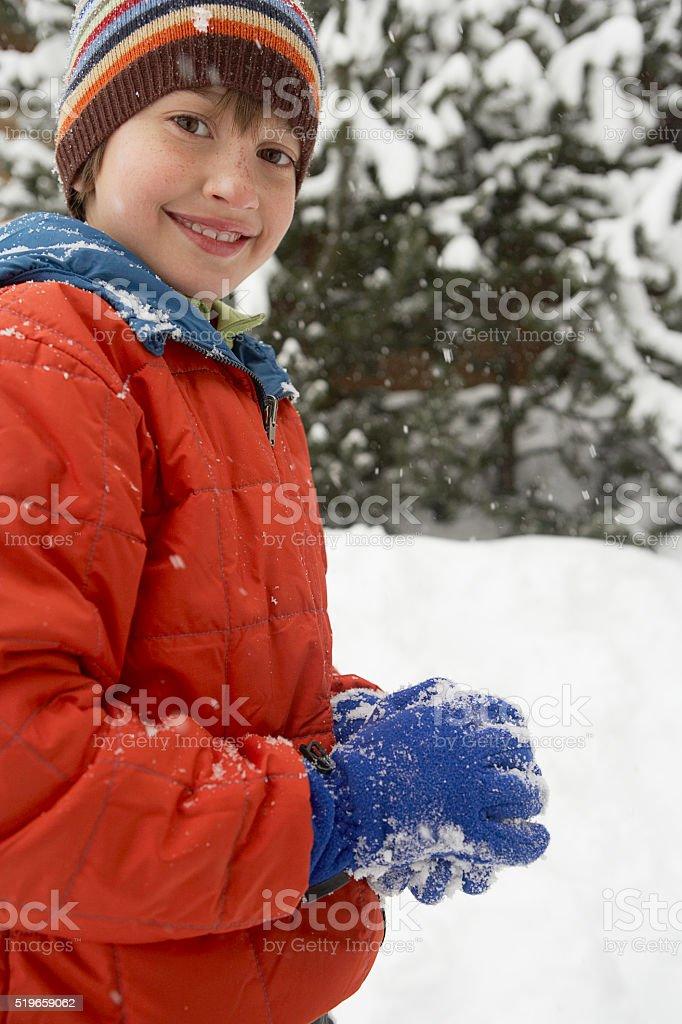 Boy packing snow ball stock photo