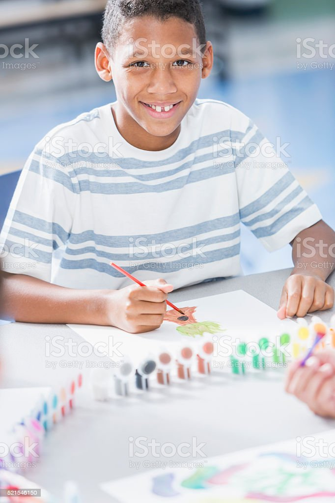 Boy painting picture in art class stock photo