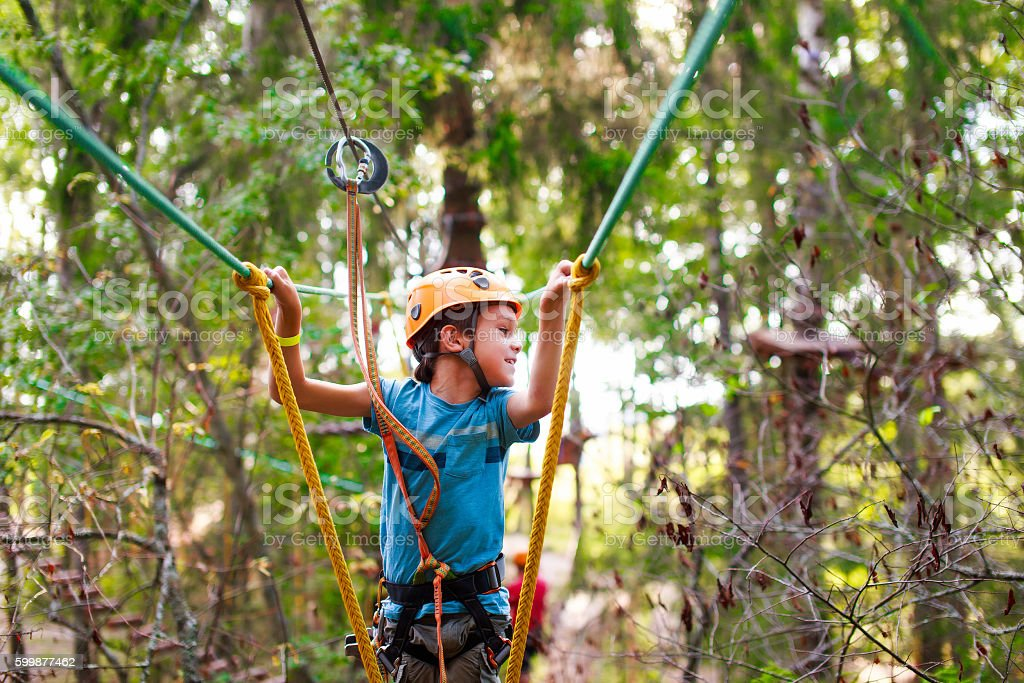 boy passes a rope obstacle course in the forest stock photo