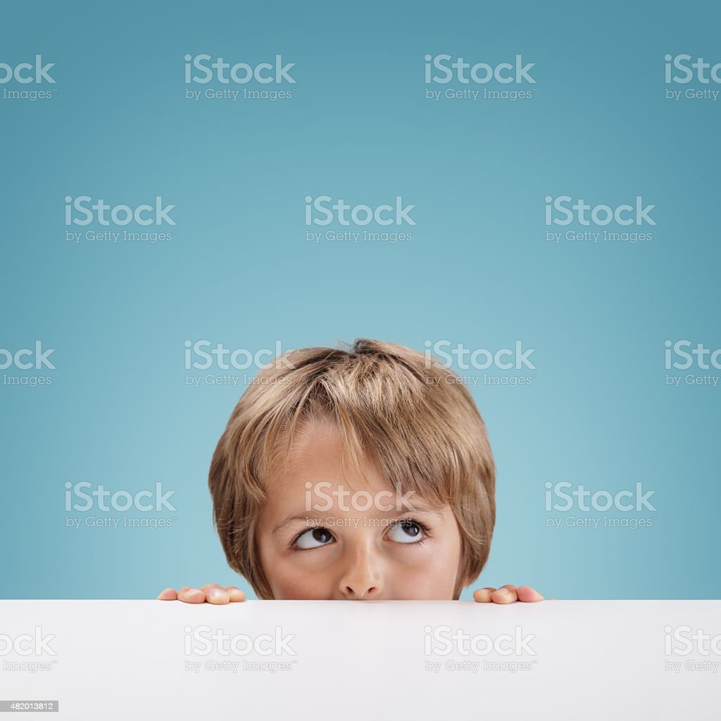Boy peeking over a white board stock photo