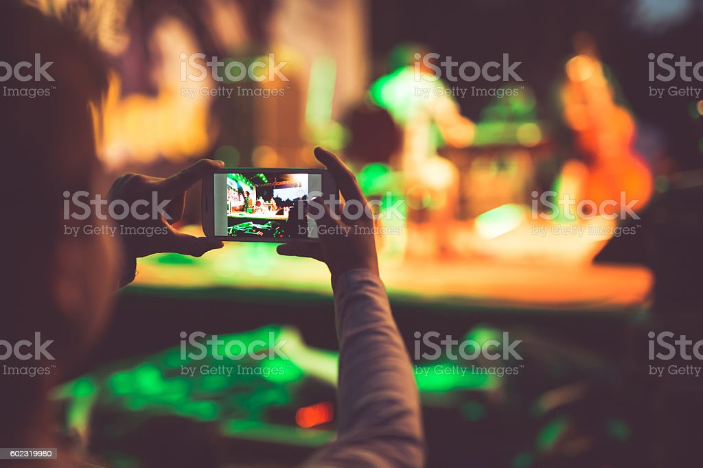 Boy photographing event with mobile phone stock photo