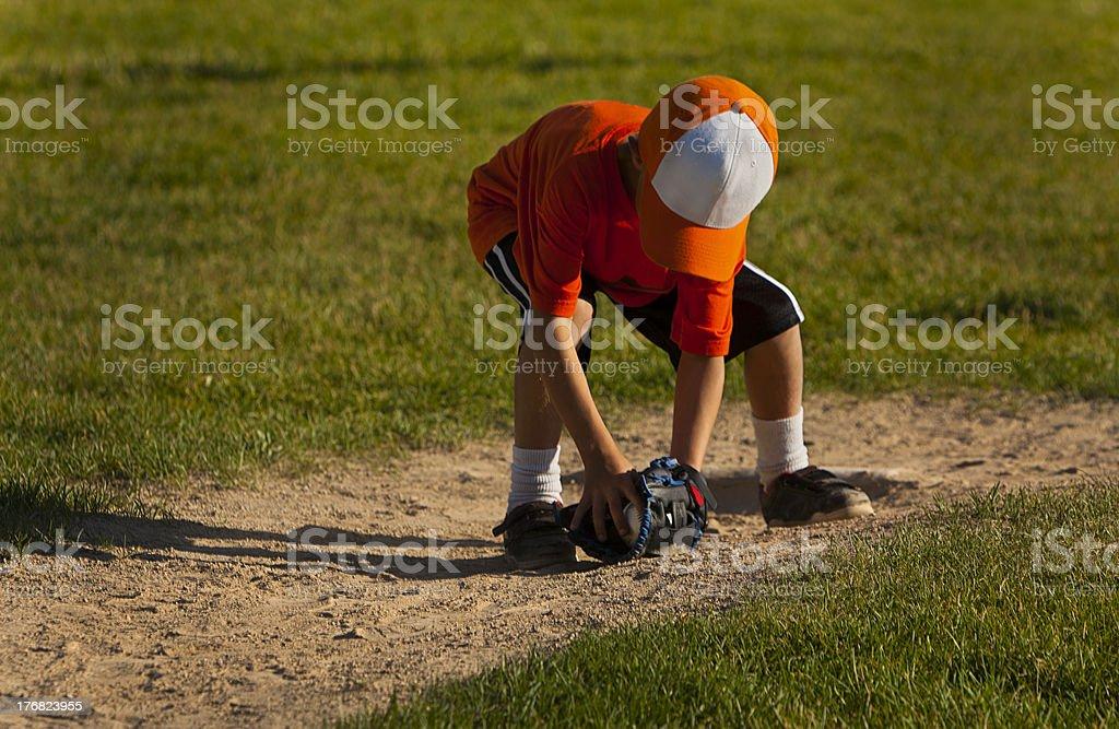 Boy picking up a ground ball. stock photo