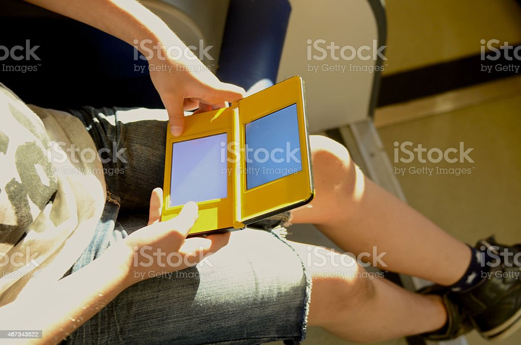 boy play with handheld videogames console stock photo
