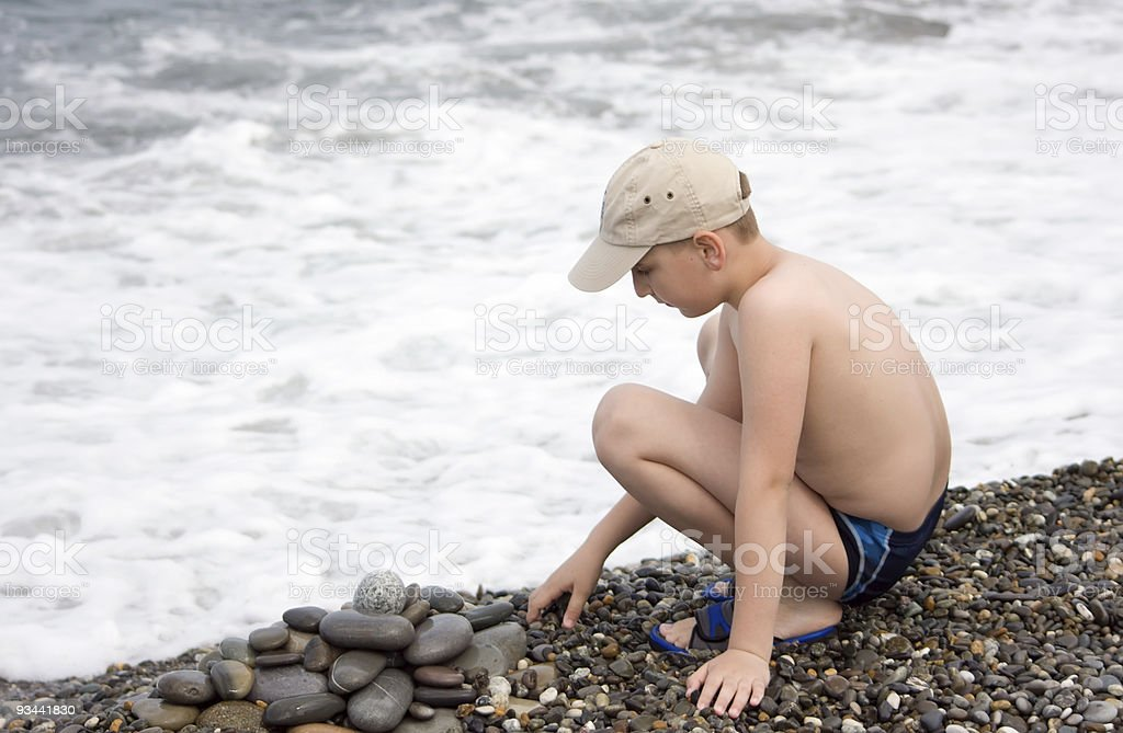 Boy play with pebbles royalty-free stock photo